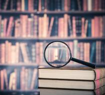 Stack of legal books with a magnifying glass and bookcase in the background.