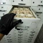 Hand opening bank drawer of money