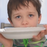 Hungry child with empty bowl