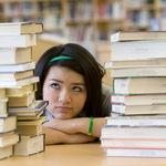 Girl frustrated by stacks of books