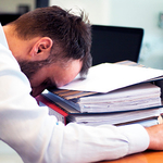 Man with head down on stack of regulatory binders