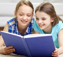 Two girls reading a book.