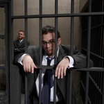 Two men in suits behind bars