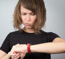 Frustrated young woman checking her watch.