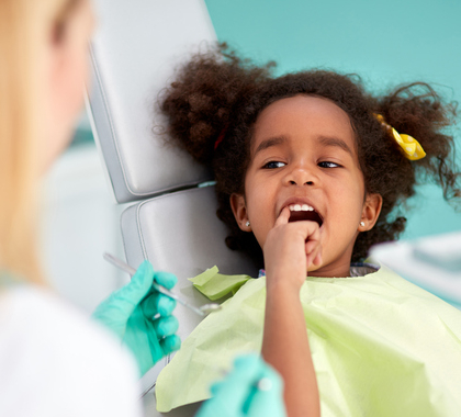 African American girl in dentist's chair with dental professional